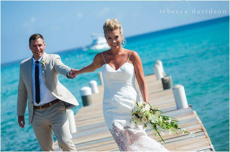 bride in white pulls groom in khaki suit along dock