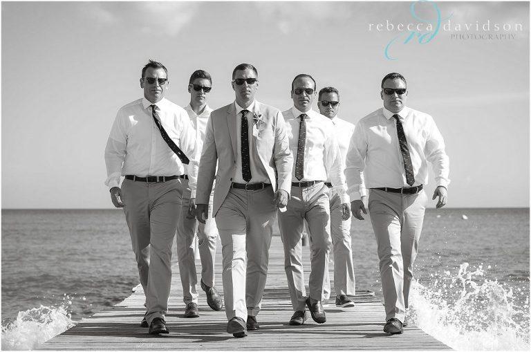 cool groomsmen walking down pier
