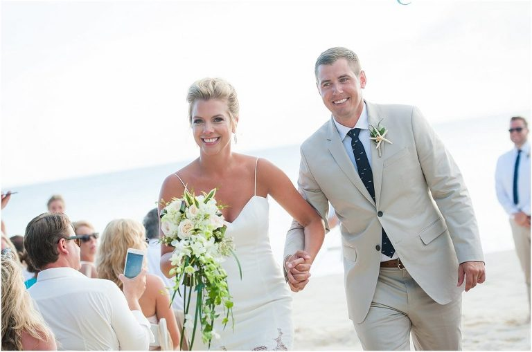 just married and walking down their beach wedding aisle
