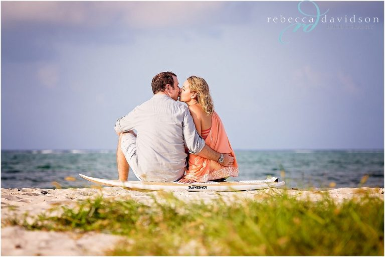 engaged couple sit on beach on surfboard