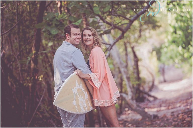 cute couple pose with surf board