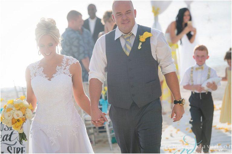groom in grey walk down aisle beach