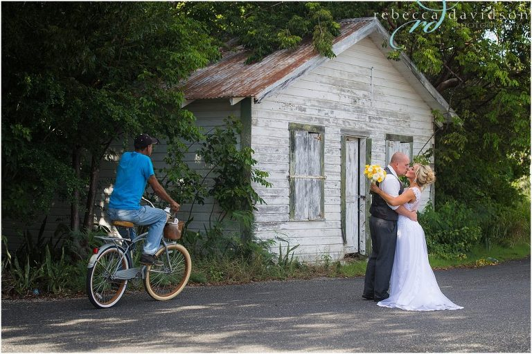 caymanian on bike with old house