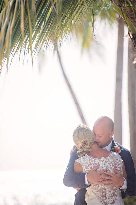 first look groom in navy kisses bride