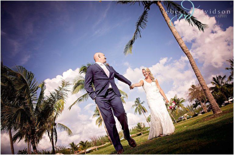 bride and groom in navy walk amongst coconut trees