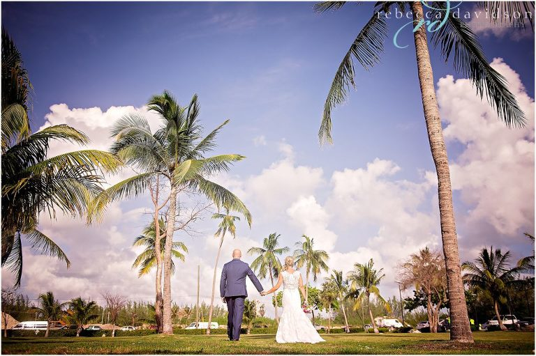 bride and groom in navy walking among coconut trees