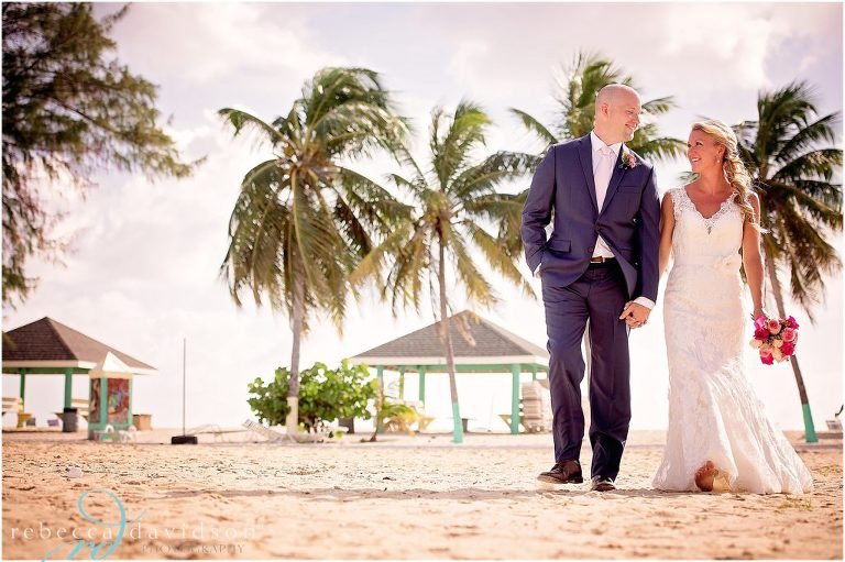 groom in navy on beach with bride
