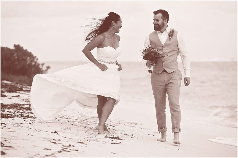 black and white of couple walking down beach